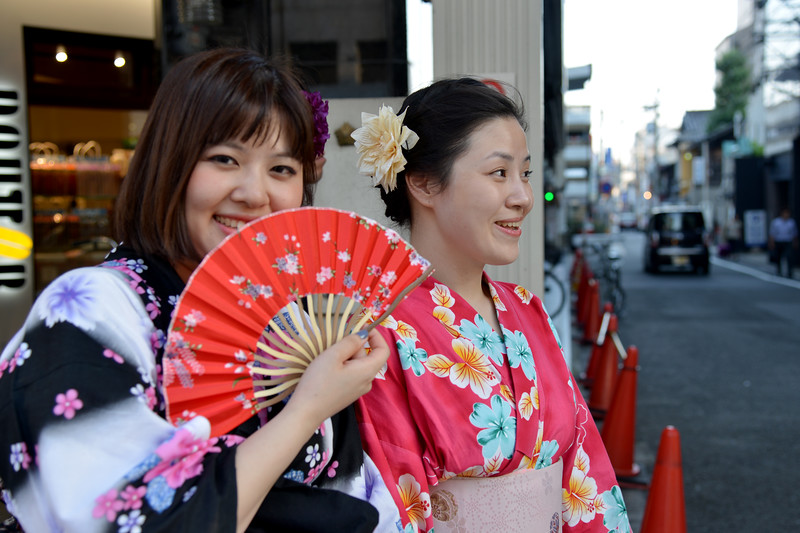 """Japanese lady dressed in the kimono (着物?). Kimono is a Japanese traditional garment. The word """"kimono"""", which literally means a """"thing to wear"""" (ki """"wear"""" and mono """"thing""""), has come to denote these full-length robes. Kimono are T-shaped, straight-lined robes worn so that the hem falls to the ankle, with attached collars and long, wide sleeves. Kimono are wrapped around the body, always with the left side over the right (except when dressing the dead for burial.), and secured by a sash called an obi, which is tied at the back. Kimono are generally worn with traditional footwear (especially zōri or geta) and split-toe socks (tabi)."""
