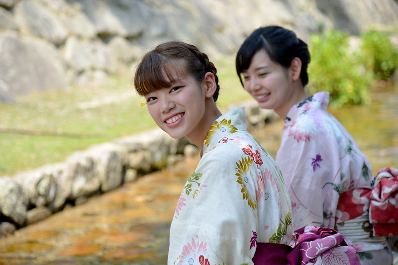 Two young Japanese ladies in traditional kimono at a water stream.<br /> <br /> Itsukushima jinja was the chief Shinto shrine (ichinomiya) of Aki Province. The shrine has been destroyed many times, but the first shrine buildings were probably erected in the 6th century. The present shrine dates from the mid-16th century, and is believed to follow an earlier design from the 12th century.That design was established in 1168, when funds were provided by the warlord Taira no Kiyomori. Miyajima (宮島町) is a town located on the island of Itsukushima in Saeki District, Hiroshima Prefecture, Japan.