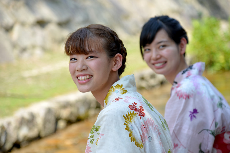 Two young Japanese ladies in traditional kimono at a cool stream in Miyajima.<br /> <br /> Itsukushima jinja was the chief Shinto shrine (ichinomiya) of Aki Province. The shrine has been destroyed many times, but the first shrine buildings were probably erected in the 6th century. The present shrine dates from the mid-16th century, and is believed to follow an earlier design from the 12th century.That design was established in 1168, when funds were provided by the warlord Taira no Kiyomori. Miyajima (宮島町) is a town located on the island of Itsukushima in Saeki District, Hiroshima Prefecture, Japan.
