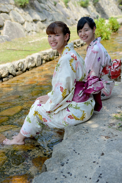 Two young Japanese ladies in traditional Kimono wetting their feet in the cool stream. <br /> <br /> Itsukushima jinja was the chief Shinto shrine (ichinomiya) of Aki Province. The shrine has been destroyed many times, but the first shrine buildings were probably erected in the 6th century. The present shrine dates from the mid-16th century, and is believed to follow an earlier design from the 12th century.That design was established in 1168, when funds were provided by the warlord Taira no Kiyomori. Miyajima (宮島町) is a town located on the island of Itsukushima in Saeki District, Hiroshima Prefecture, Japan.