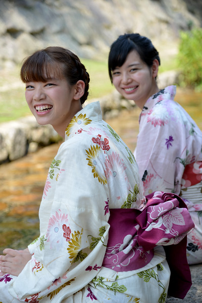 Young Japanese ladies in traditional Kimono wetting their feet on a hot day in the cool stream.<br /> <br /> Itsukushima jinja was the chief Shinto shrine (ichinomiya) of Aki Province. The shrine has been destroyed many times, but the first shrine buildings were probably erected in the 6th century. The present shrine dates from the mid-16th century, and is believed to follow an earlier design from the 12th century.That design was established in 1168, when funds were provided by the warlord Taira no Kiyomori. Miyajima (宮島町) is a town located on the island of Itsukushima in Saeki District, Hiroshima Prefecture, Japan.