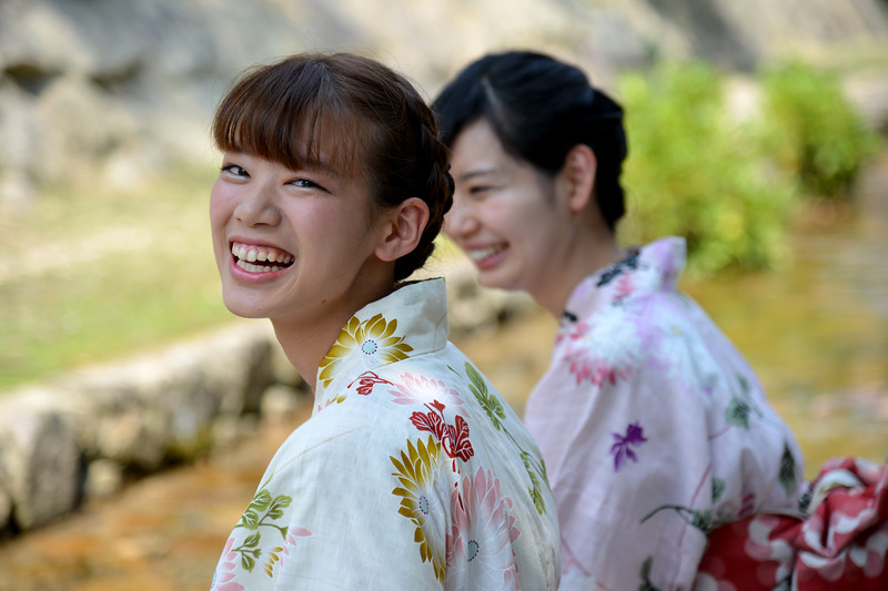 Two young Japanese ladies in traditional kimono all smiles when cooling their feet in a stream in Miyajima.<br /> <br /> Itsukushima jinja was the chief Shinto shrine (ichinomiya) of Aki Province. The shrine has been destroyed many times, but the first shrine buildings were probably erected in the 6th century. The present shrine dates from the mid-16th century, and is believed to follow an earlier design from the 12th century.That design was established in 1168, when funds were provided by the warlord Taira no Kiyomori. Miyajima (宮島町) is a town located on the island of Itsukushima in Saeki District, Hiroshima Prefecture, Japan.