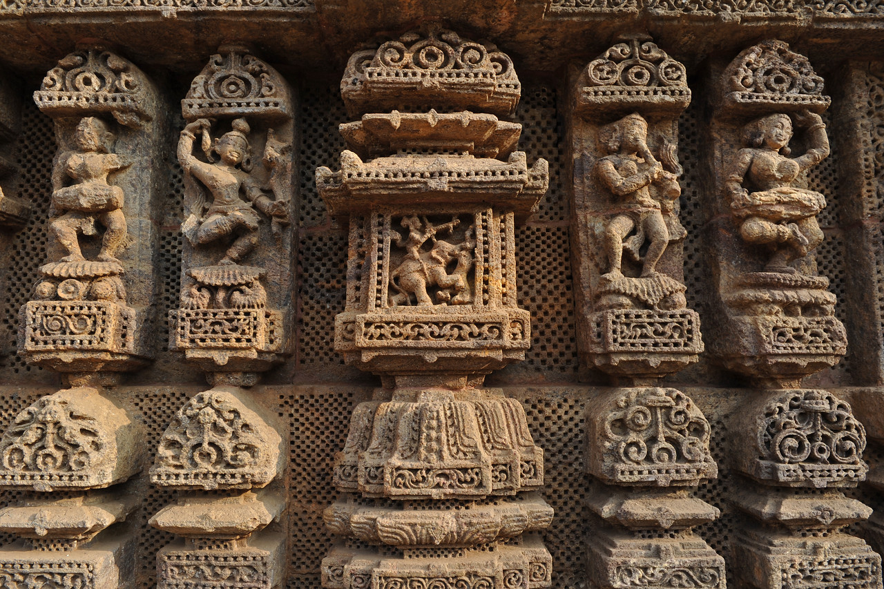 Exquisite details in stone sculptures at Konark Temple.<br /> <br /> Konark Sun Temple in Orissa belongs to the Kalinga school of Indian temples and was constructed by King Narasimhadeva of the Eastern Ganga Dynasty in the 13th Century. This world heritage site temple takes the form of a colossal chariot of Surya (Sun) drawn by seven spirited horses on twelve pairs of exquitely decorated wheels. Surya has been a popular deity in India since the Vedic perios. Thousands of sculptured images depict deities, celestial and human musicians, dancers, lovers, and myriad scenes of courtly life, ranging from hunts and military battles to the pleasures of courtly relaxation. The temple is famous for its erotic stone sculptures, which can be found primarily on the second level of the porch structure.