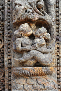 A couple in loving embrase, kissing each other. Many erotic art forms depicted on the stone walls of Konark Temple.  Konark Sun Temple in Orissa belongs to the Kalinga school of Indian temples and was constructed by King Narasimhadeva of the Eastern Ganga Dynasty in the 13th Century. This world heritage site temple takes the form of a colossal chariot of Surya (Sun) drawn by seven spirited horses on twelve pairs of exquitely decorated wheels. Surya has been a popular deity in India since the Vedic perios. Thousands of sculptured images depict deities, celestial and human musicians, dancers, lovers, and myriad scenes of courtly life, ranging from hunts and military battles to the pleasures of courtly relaxation. The temple is famous for its erotic stone sculptures, which can be found primarily on the second level of the porch structure.