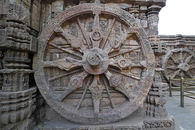 Very intricate carvings done on the gigantic stone wheels at Konark Temple.  Konark Sun Temple in Orissa belongs to the Kalinga school of Indian temples and was constructed by King Narasimhadeva of the Eastern Ganga Dynasty in the 13th Century. This world heritage site temple takes the form of a colossal chariot of Surya (Sun) drawn by seven spirited horses on twelve pairs of exquitely decorated wheels. Surya has been a popular deity in India since the Vedic perios. Thousands of sculptured images depict deities, celestial and human musicians, dancers, lovers, and myriad scenes of courtly life, ranging from hunts and military battles to the pleasures of courtly relaxation. The temple is famous for its erotic stone sculptures, which can be found primarily on the second level of the porch structure.