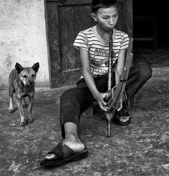 "Young boy playing the Khene.<br /> The Khene is a reed musical instrument so loved and readily recognised by the people of Laos that it has become part of their every day life similar to other instrumental terms such as table, chair, food. Many Lao have learned the word ""khene"" or heard the instrument being played since early childhood, but few know much about its origin or how to play it. However, some Lao scholars have been able to retrace where the word ""Khene"" came from in the form of legend.<br /> It is said that long ago, there was a Lao widow who liked to imitate the birds' songs. One day, she followed the well-known hunters of her village to a hunting expedition into the deep forest which took many weeks. <br /> To record this special sound, the widow made a wind instrument using the mouth to blow air into. <br /> <br /> Napho village, Laos, 2010."