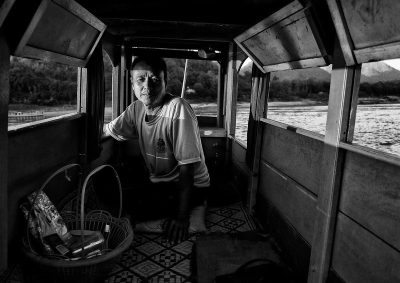Fisherman in his boat on the Mekong river.<br /> <br /> Luang Prabang, Laos, 2010.