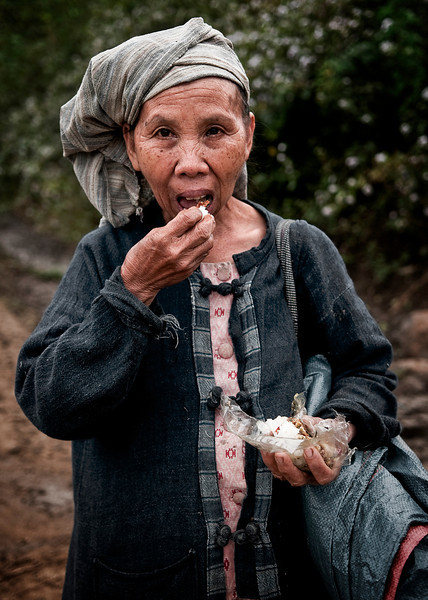 Woman eating sticky rice on her way to work in the fields outside the mountain village of Naxao.<br /> <br /> Laos, 2010.