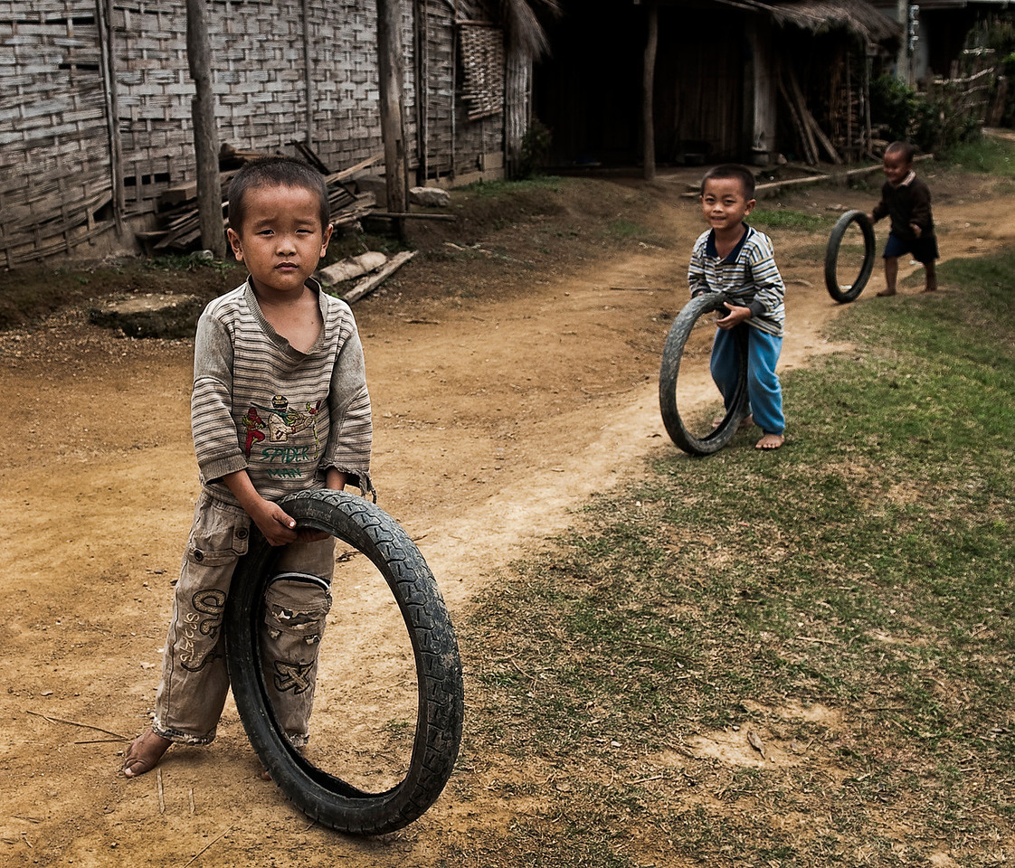 Children playing with old tires in the village of Napho.<br /> <br /> Laos, 2010.