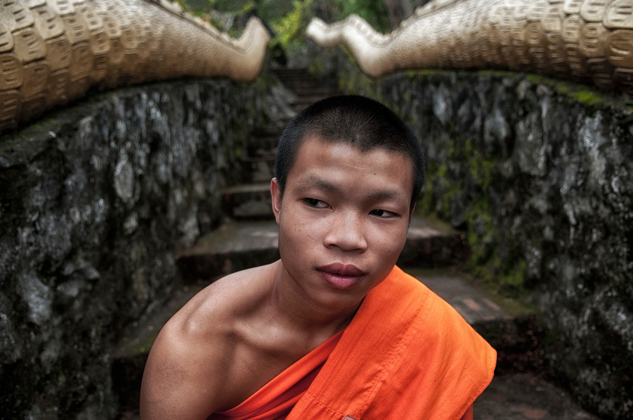 The minimum age for ordaining as a Buddhist monk is 20 years, reckoned from conception. However, boys under that age are allowed to ordain as novices (samanera), performing a ceremony such as Shinbyu in Burma. Novices shave their heads, wear the yellow robes, and observe ten basic precepts. Although no specific minimum age for novices is mentioned in the scriptures, traditionally boys as young as seven are accepted. This tradition follows the story of the Lord Buddha's son, Rahula, who was allowed to become a novice at the age of seven. Monks follow 227 rules of discipline.<br /> <br /> Monk, Luang Prabang, Laos, 2010.