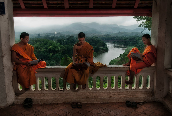 "Lao Buddhist are very devout and almost every Lao man joins a monastery, or temple, for at least a short period of time. Many men also become monks for the rest of their lives. Most people donate food to the monks to gain merit and improve their karma. The temples of Laos were once seen as ""Universities"" for monks. Lao monks are highly respected and revered in Lao communities. These monks living on Mount Phou start the day early, at about five in the morning whan they take to the streets to receive alms. They then return to the temple were they have breakfast. After breakfast they take a few hours to study Geography and English before commencing more spiritual duties.   Luang Prabang, Laos, 2010."