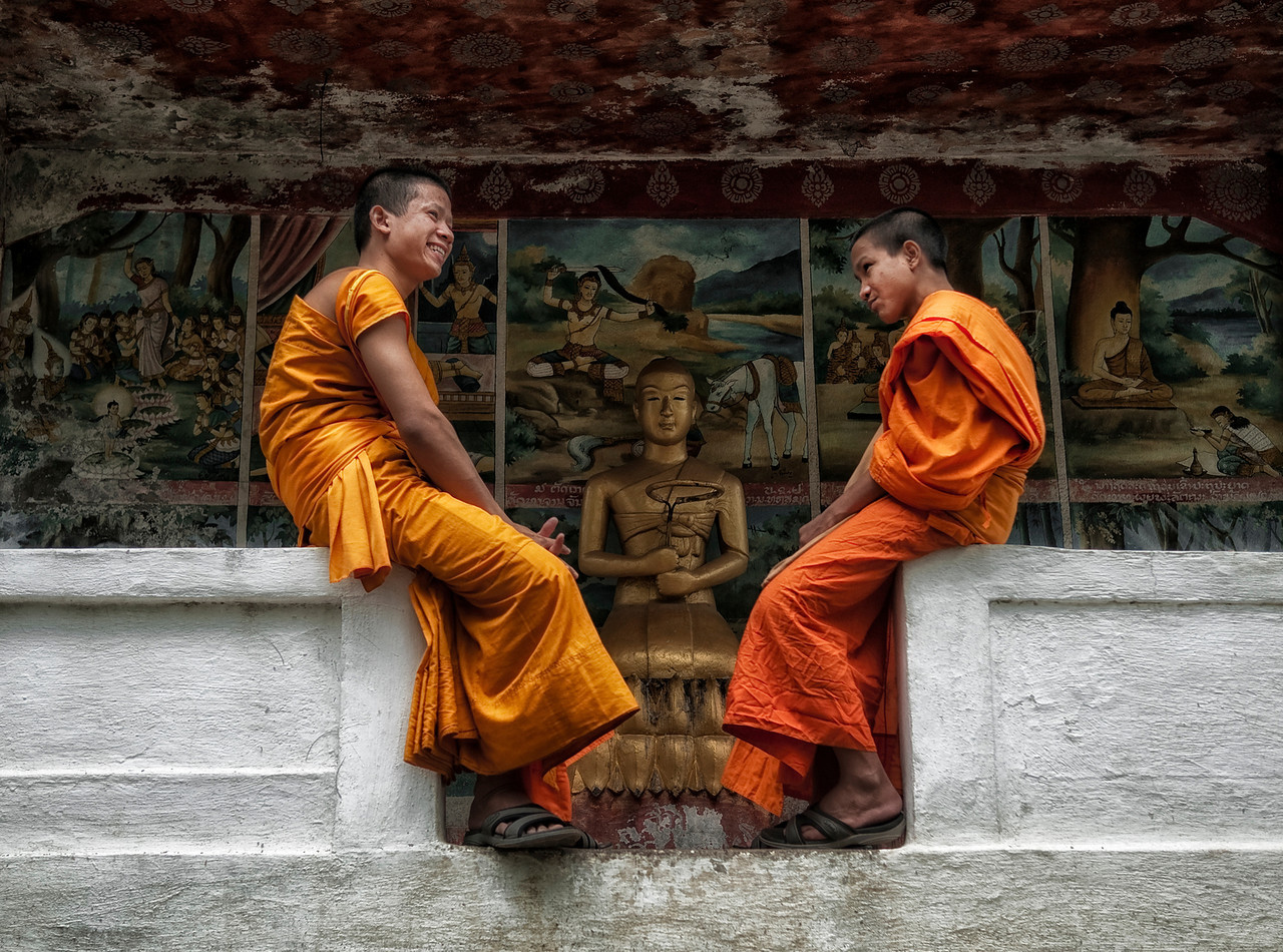 Monks in front of a Buddha statue.<br /> <br /> Luang Prabang, Laos, 2010.
