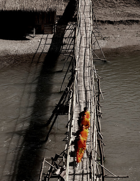 Monks crossing a Bamboo bridge.<br /> <br /> Luang Prabang, Laos, 2010.