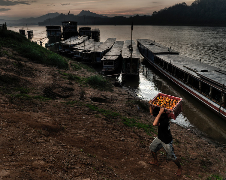 Man unloading oranges from a cargo boat on the Mekong River.<br /> Because of its mountainous topography and lack of development, Laos has few reliable transportation routes. This inaccessibility has historically limited the ability of any government to maintain a presence in areas distant from the national or provincial capitals and has limited interchange and communication among villages and ethnic groups. The Mekong and Nam Ou are the only natural channels suitable for large-draft boat transportation, and from December through May low water limits the size of the craft that may be used over many routes. Laotians in lowland villages located on the banks of smaller rivers have traditionally traveled in pirogues for fishing, trading, and visiting up and down the river for limited distances. Otherwise, travel is by ox-cart over level terrain or by foot. The steep mountains and lack of roads have caused upland ethnic groups to rely entirely on pack baskets and horse packing for transportation.<br /> <br /> Luang Prabang, Laos, 2010.