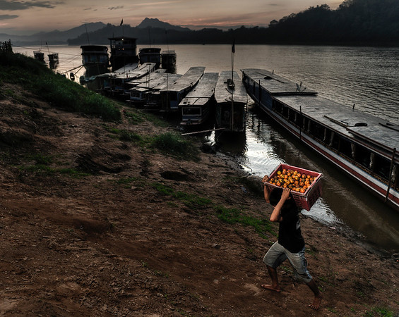 Man unloading oranges from a cargo boat on the Mekong River. Because of its mountainous topography and lack of development, Laos has few reliable transportation routes. This inaccessibility has historically limited the ability of any government to maintain a presence in areas distant from the national or provincial capitals and has limited interchange and communication among villages and ethnic groups. The Mekong and Nam Ou are the only natural channels suitable for large-draft boat transportation, and from December through May low water limits the size of the craft that may be used over many routes. Laotians in lowland villages located on the banks of smaller rivers have traditionally traveled in pirogues for fishing, trading, and visiting up and down the river for limited distances. Otherwise, travel is by ox-cart over level terrain or by foot. The steep mountains and lack of roads have caused upland ethnic groups to rely entirely on pack baskets and horse packing for transportation.  Luang Prabang, Laos, 2010.