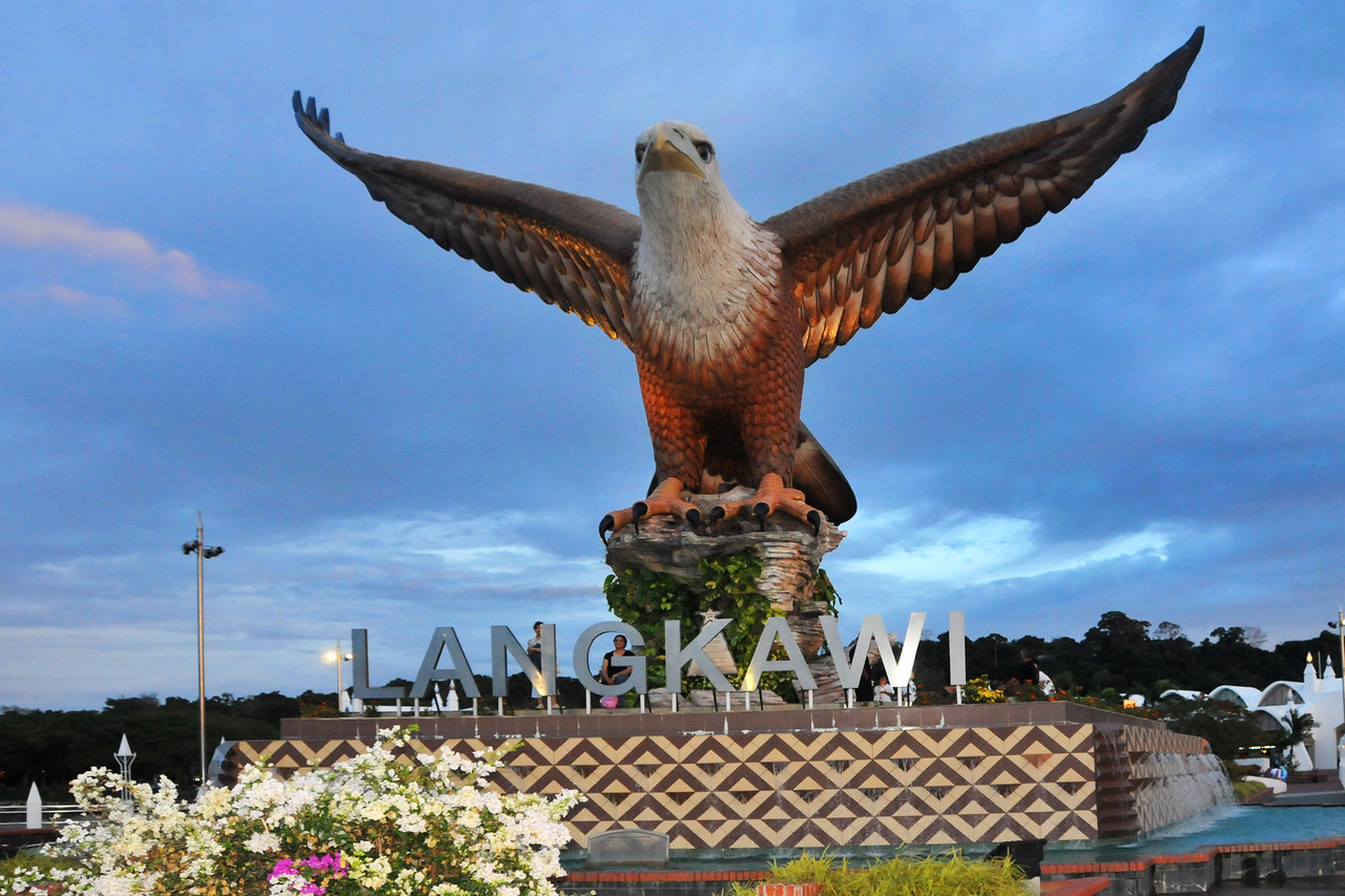 """Eagle Square / Dataran Lang is Langkawi's most prominent landmark for visitors arriving by sea and also a place visited by others. Situated near the Kuah jetty, the main attraction of the square is the magnificent statue of the reddish brown eagle majestically poised for flight. According to local folklore, the name Langkawi itself is derived from- the eagle or """"helang"""". In old Malay, """"kawi"""" denotes reddish brown - hence, Langkawi means reddish brown eagle!"""