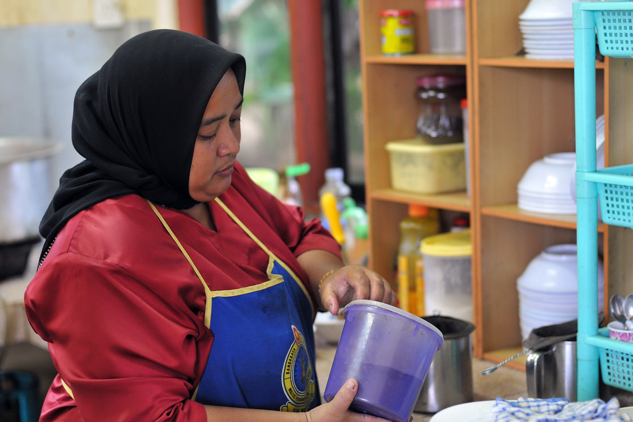 Food and tea being prepared in a small kitchen at the Malay village recreated with houses, music, and dance in Langkawi, Malaysia