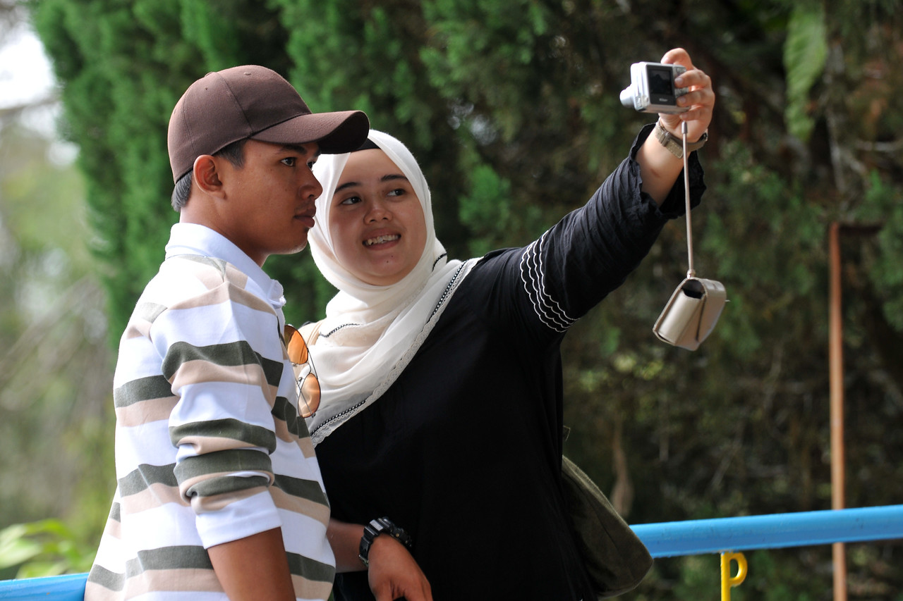 Say Cheese! Malay couple taking pictures at Penang Hill, Malaysia