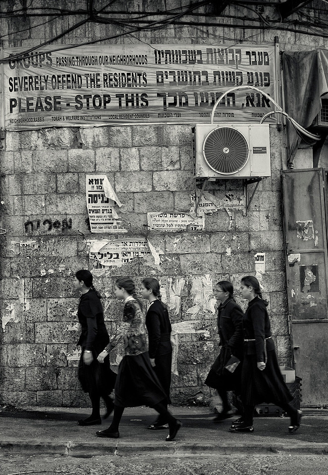 "Mea Shearim is an insulated neighbourhood in the heart of Jerusalem. With its overwhelmingly Haredi population, the streets retain the flavor of an East European shtetl Life which revolves around strict adherence to Jewish law, prayer, and the study of Jewish texts. Traditions in dress may include black frock coats and black or fur-trimmed hats for men and long-sleeved, modest clothing for women. ""Modesty"" posters in Hebrew and English are hung at every entrance to Mea Shearim. When visiting the neighborhood, women and girls are asked to wear what is deemed to be modest dress (knee-length skirts or longer, no plunging necklines or midriff tops, no sleeveless blouses or bare shoulders) and tourists are requested not to arrive in large, conspicuous groups. During the Shabbat (from sunset Friday until it is completely dark on Saturday night), visitors should refrain from smoking, photography, driving or use of mobile phones. When entering synagogues, men should cover their heads."
