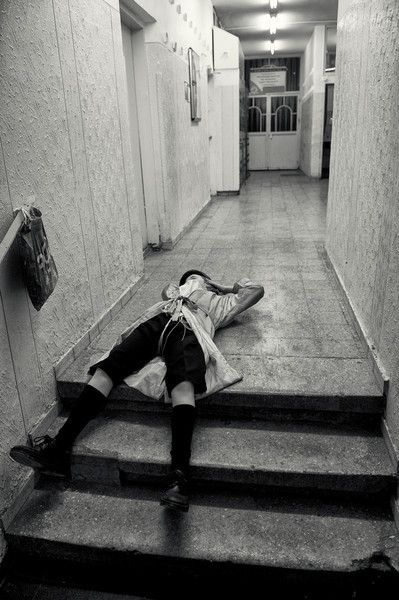 A drunk youth lies on the ground on a public toilett during purim.