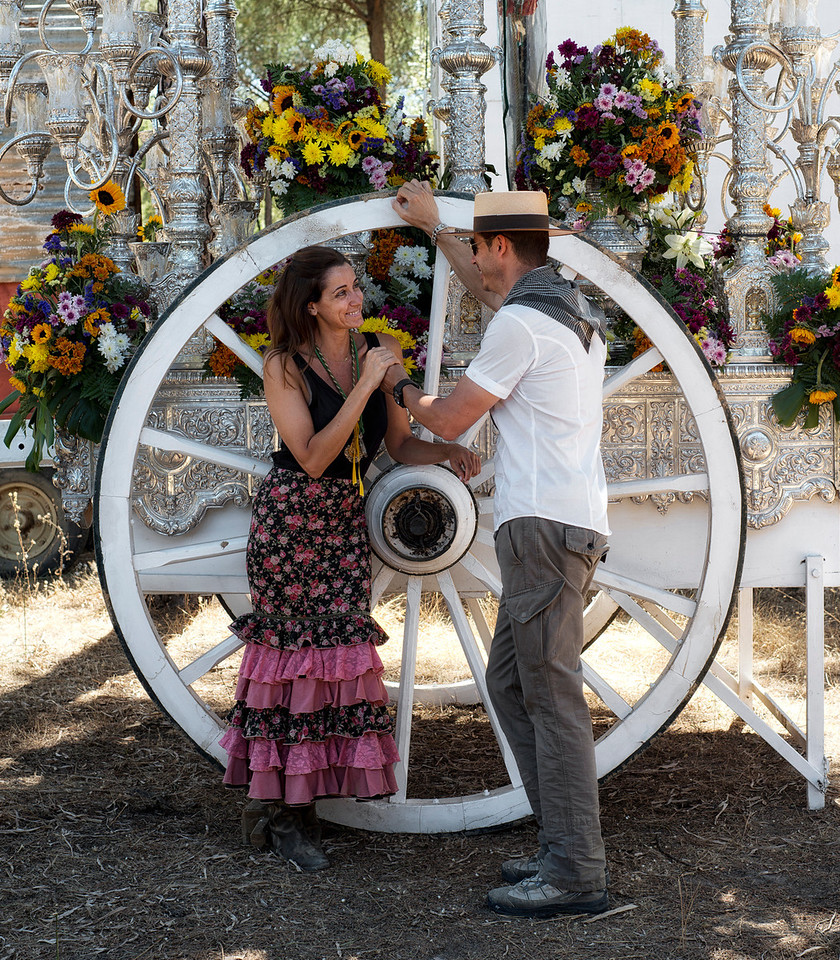 """With Spring in the air, dancing and singing around campfires and the romance of travelling by horse and carriage it's little wonder that so many Rocieros are actually """"Made In El Rocio"""". <br /> This couple take an intimate moment behind a a wagon away from the travelling troop."""