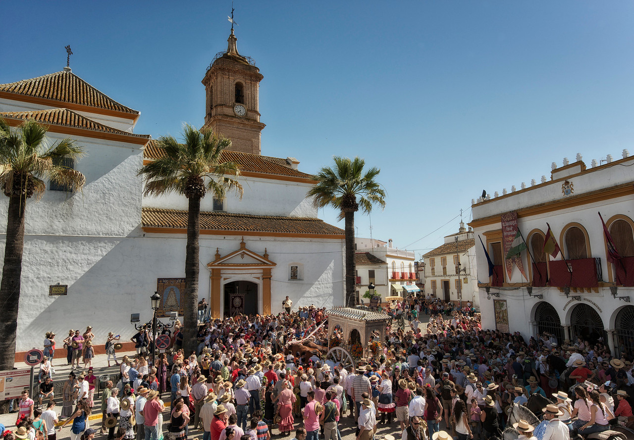 "It is customary for the hermandades to stop at the town of Villamanrique. Oxen are then made to pull the cart carrying the image of the Holy Virgin up a staircase to the entrance of the local church ""pictured above"" and receive a blessing from the priest."