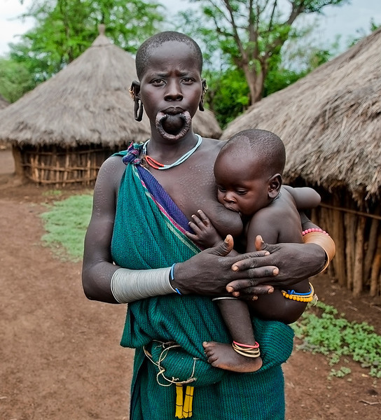 Meet Nachuna and her son Olabile from the Surma tribe. Nachuna runs her own household and owns her own fields. She is free to spend the profits from the crops as she whishes as opposed to women in other more male dominated tribes. Nachuna sometimes wears a lip plate.  At the point of puberty she had her bottom teeth removed in order to get the lower lip pierced. Once the lip was pierced, it was stretched and a lip plate was inserted in the hole of the piercing. She, like all Surma women, sees this as sign of beauty. The size of the lip plate also indicates her value in cattle on the day of her wedding day. The bigger the plate, the more valuable she becomes.