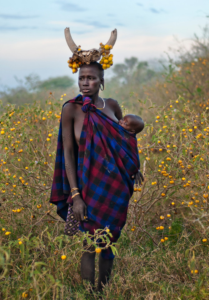 Meet Magantu and her baby girl Bartui from the Mursi tribe. Magantu chose not to pierce her lips for a lip plate like most Mursi women. She does however use the ear plates and makes creative use of the surrounding nature to adorn herself.  Magantu lives in a tiny hamlet consisting of a handful of straw and mud huts. There are other such hamlets nearby, but no villages or towns for hundreds of kilometers. The Ethiopian government has recently opened a very basic and somewhat unhygienic clinic close to Magantu's home. It has a handful of government civil servants who offer medical assistance. The problem is that most of the medicine on offer has a cost, unless it's directly supplied by an NGO (non-governmental organizations).  Magantu, like most other people in her area, owns a couple of cows. The milk from them is used for drinking and to mix with maize into a porridge. Blood from the cow is also drunk for extra strength. Magantu, unlike other Mursi living nearer to towns or water supplies, has no way of earning money. Even selling a cow is impossible since the nearest market is hundreds of kilometers away, and there is no means of transport. Therefore, Magantu simply can't afford the medicine on offer in the clinic.