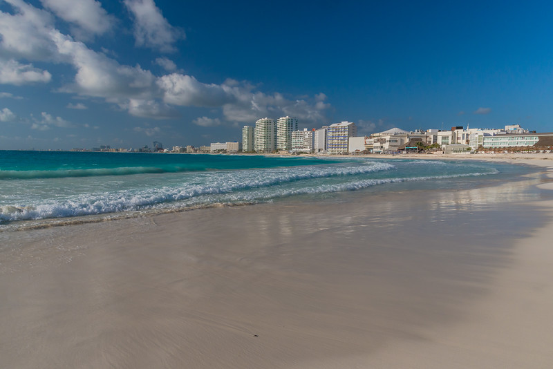 The gleaming white buildings of the Cancun Hotel Zone rise above sandy beaches and the aqua waves of the Caribbean Sea.