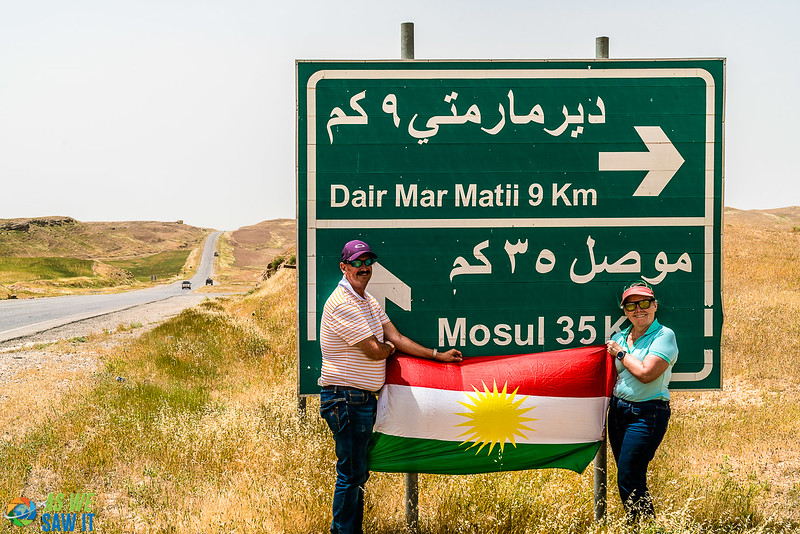 We pose with a Kurdish flag in front of a road sigh. Sigh says Dair Mar Matil 9 km, Mosul, 35 km