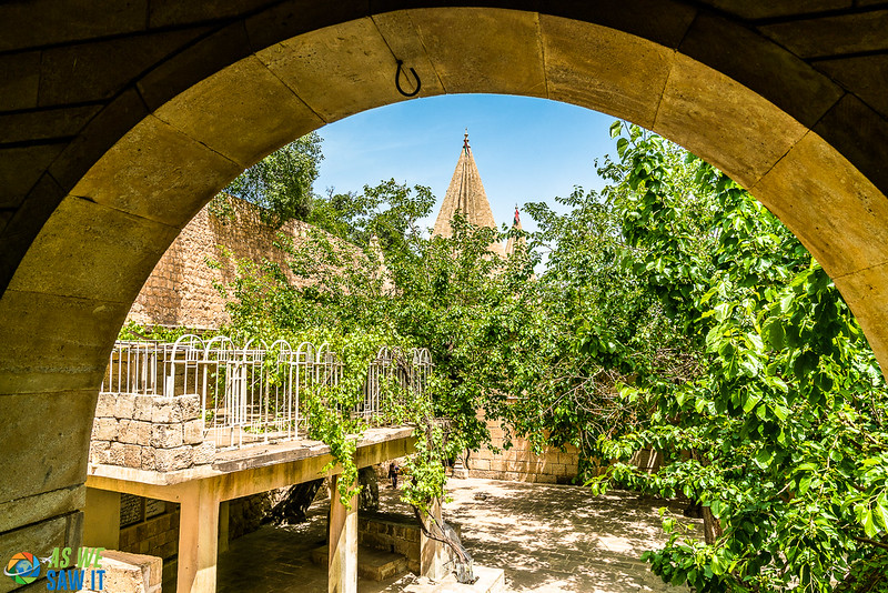 Archway frames a rooftop terrace and the tips of Yazidi's iconic rooftops