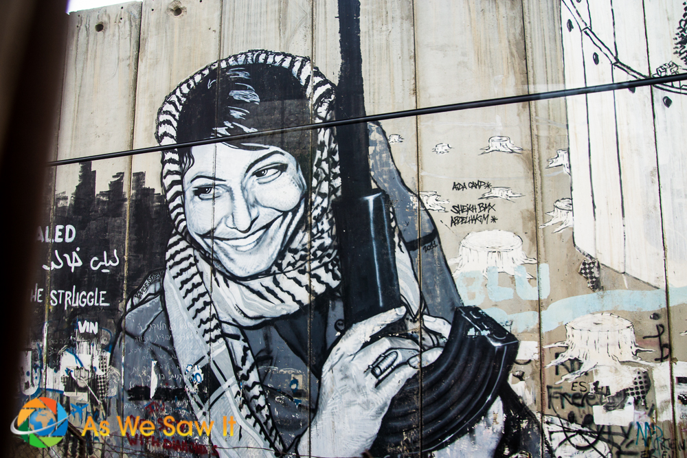Graffiti of a Palestinian woman holding a rifle and wearing a ring with a bullet on it.