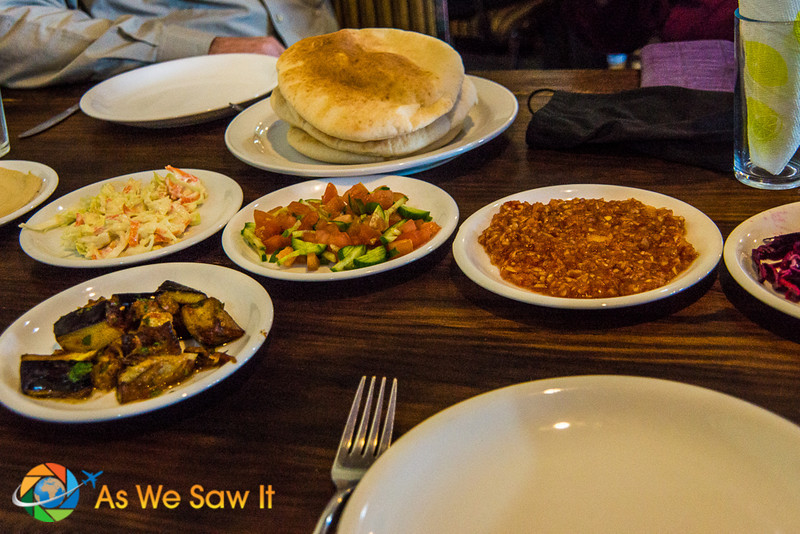 A pre-meal spread includes slaws, roasted eggplant, tomato-cucumber salad, and pita