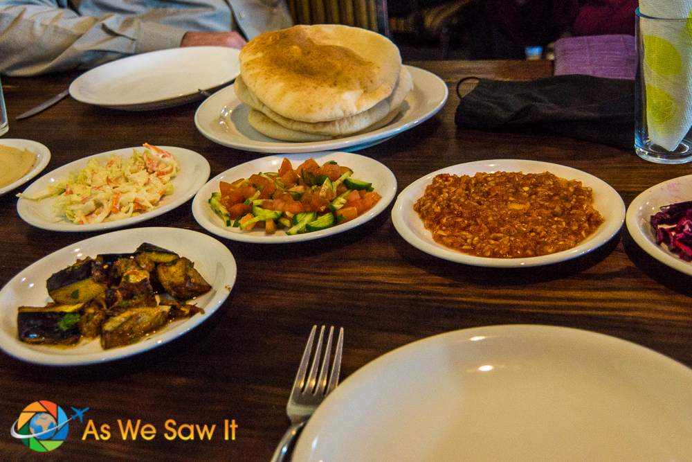 pre-meal spread includes slaws, roasted eggplant, tomato-cucumber salad, and pita