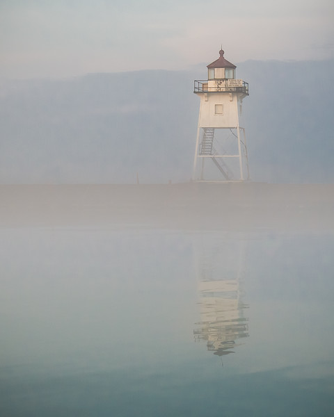 Simple white lighthouse emerges from the morning fog on Lake Superior in Grand Marias, Minnesota, USA.
