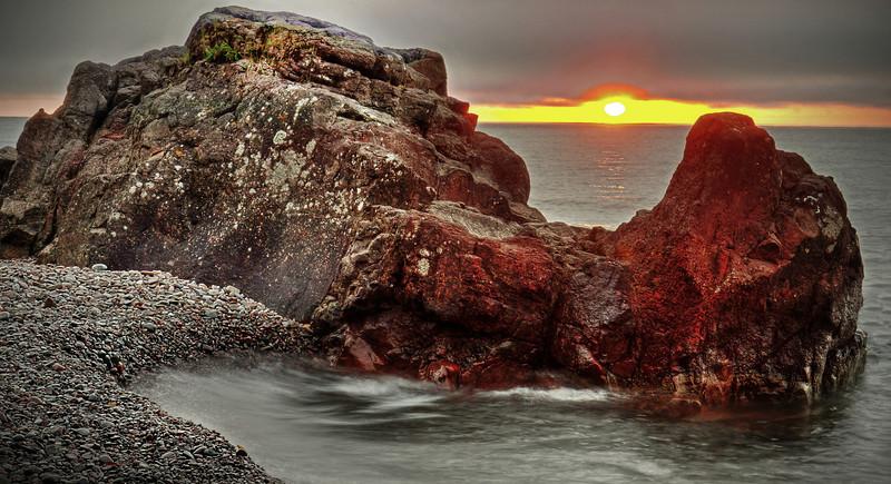 Orange glow of sunrise at the Lutsen Resort beach on Lake Superior rocky shores, #0472