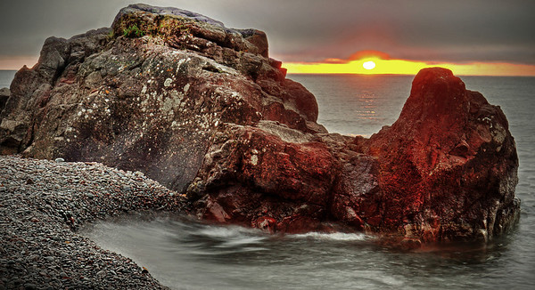 Orange glow of sunrise at the Lutsen Resort beach on Lake Superior rocky shores, #0472