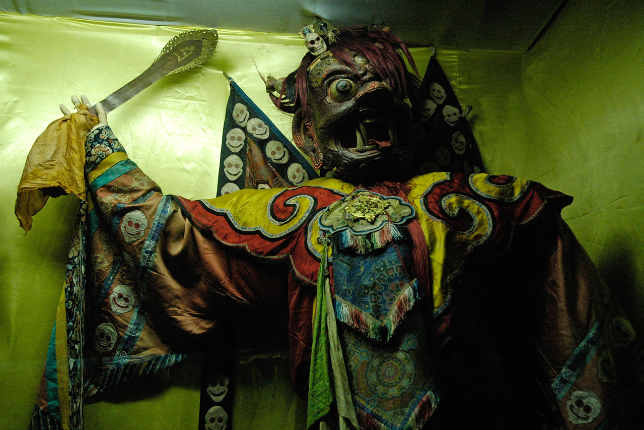 """Masks, dress and other display at the Danzanravjaa Museum which was established in 1991 in honour of the fifth Goviin Dogshin Noyon Khutagt (""""Terrible Noble Saint of the Gobi""""), one of the greatest and most unusual intellectuals in Mongolian history. The museum preserves and displays Danzanravjaa's original artistic works and literary manuscripts, along with his books, religious items, theatrical costumes, personal possessions, and similar objects illustrating his life and work.<br /> <br /> The nineteenth century Lama Danzanravjaa was one of the most creative, colorful and enigmatic characters in Mongolian history. He was an accomplished artist, poet, scholar, playwright, songwriter, linguist, collector, traveler, martial artist, and herbal medic as well as Buddhist leader in the Gobi. He spent months at a time in prayer and creative solitude in caves or in his special ger, which, to avoid interruption, he had built without a door. At other times he was a hot-tempered, drunken party animal, organizing and participating in wild orgies at his temple. In his lifetime he was considered a living god and at his death a martyr. Today Mongolians are just discovering his full dimensions as after his death in 1856, Danzanravjaa's legend and surviving works went underground for 135 years."""