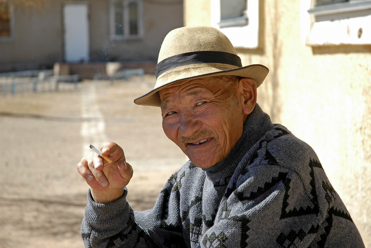 Portraits of an old man smoking while waiting outside a rural hospital in Central Mongolia.
