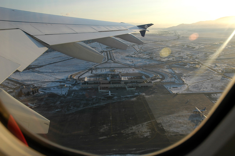 Ariel view of Ulaan Baator Airport partly covered by snow as the early morning Sun rises in UB city, Mongolia.