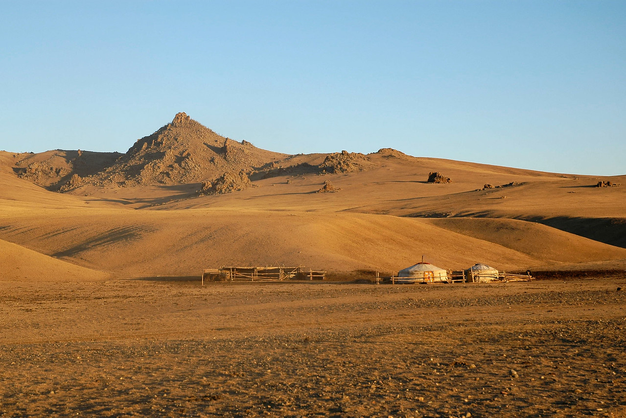 Mongolian Ger (Yurt with portable felt dwelling) with clear blue skies above and a vast expanse of land in Gobi desert. One can drive long distances without coming across any people or mammals. Occasionally one comes across a ger and a few family members. Rural Central Mongolia. <br /> <br /> Mongolian Ger (Yurt) in Gobi desert. Central Mongolia. <br /> <br /> Traditional gers consist of a circular wooden frame carrying a felt cover. The felt is made from the wool of the flocks of sheep that accompany the pastoralists. The timber to make the external structure is not to be found on the treeless steppes, and must be traded.<br /> <br /> The frame consists of one or more lattice wall-sections, a door-frame, roof poles and a crown. Some styles have one or more columns to support the crown. The (self-supporting) wood frame is covered with pieces of felt. Depending on availability, the felt is additionally covered with canvas and/or sun-covers. The frame is held together with one or more ropes or ribbons. The structure is kept under compression by the weight of the covers, sometimes supplemented by a heavy weight hung from the center of the roof. They vary regionally, with straight or bent roof-poles, different sizes, and relative weight.<br /> <br /> It is designed to be dismantled and the parts carried on camels or yaks to be rebuilt on another site.