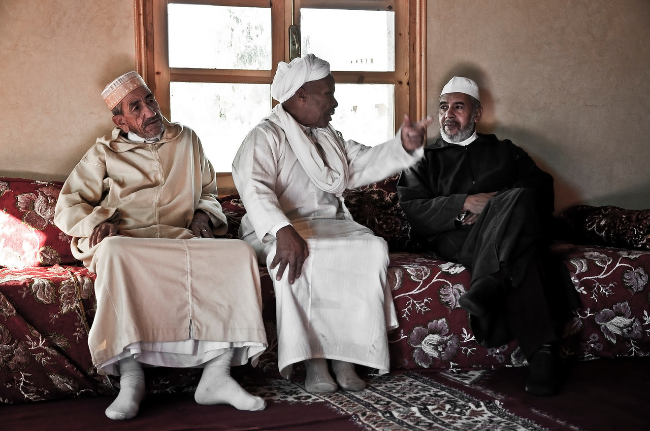Descendant of the local Caid (leader), and now head of the extended family at the Kasbah Caid Ali (far left). Has just returned from a holy trip to Mecca with his two friends. There is now much to debate.  <br /> <br /> Agdz, Morocco, 2010.
