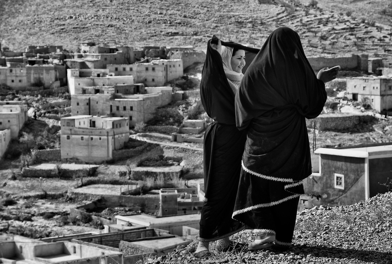Small Berber mountain village north of Tafraoute. Women here cover up there faces behind there veils. This young and unmarried girls still retain the innocence needed to uncover discreetly in the presence of strangers. <br /> <br /> Morocco, 2010.
