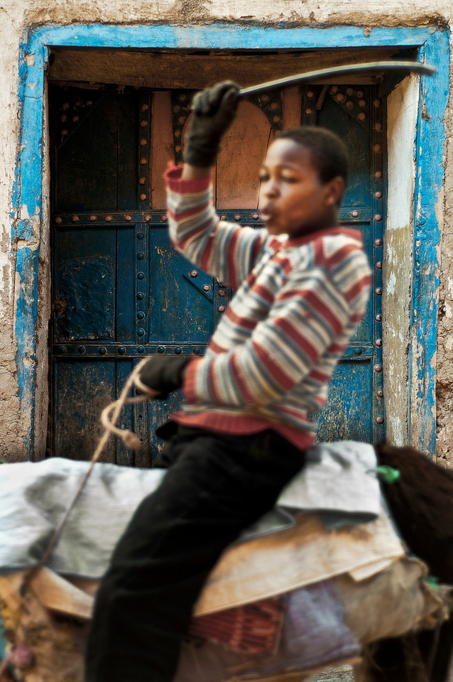 Boy on his donkey in the town of Agdez.<br /> <br /> Morocco, 2010.