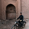 A man riding his bike past a Ksar in the skoura palmeraie.<br /> <br /> Skoura, Morocco, 2018
