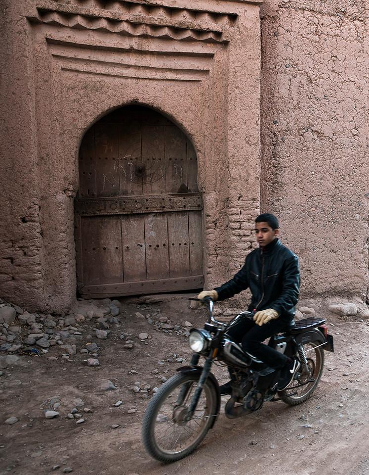 A man riding his bike past a Ksar in the skoura palmeraie.<br /> <br /> Skoura, Morocco, 2018
