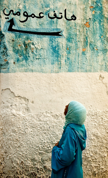 woman reading a street sign in Fez El Bali.<br /> <br /> Fez, Morocco,2010