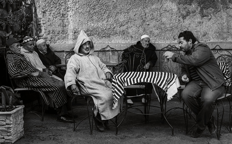 Men sitting outside a cafe.<br /> <br /> Chefchaouen, Morocco, 2018.