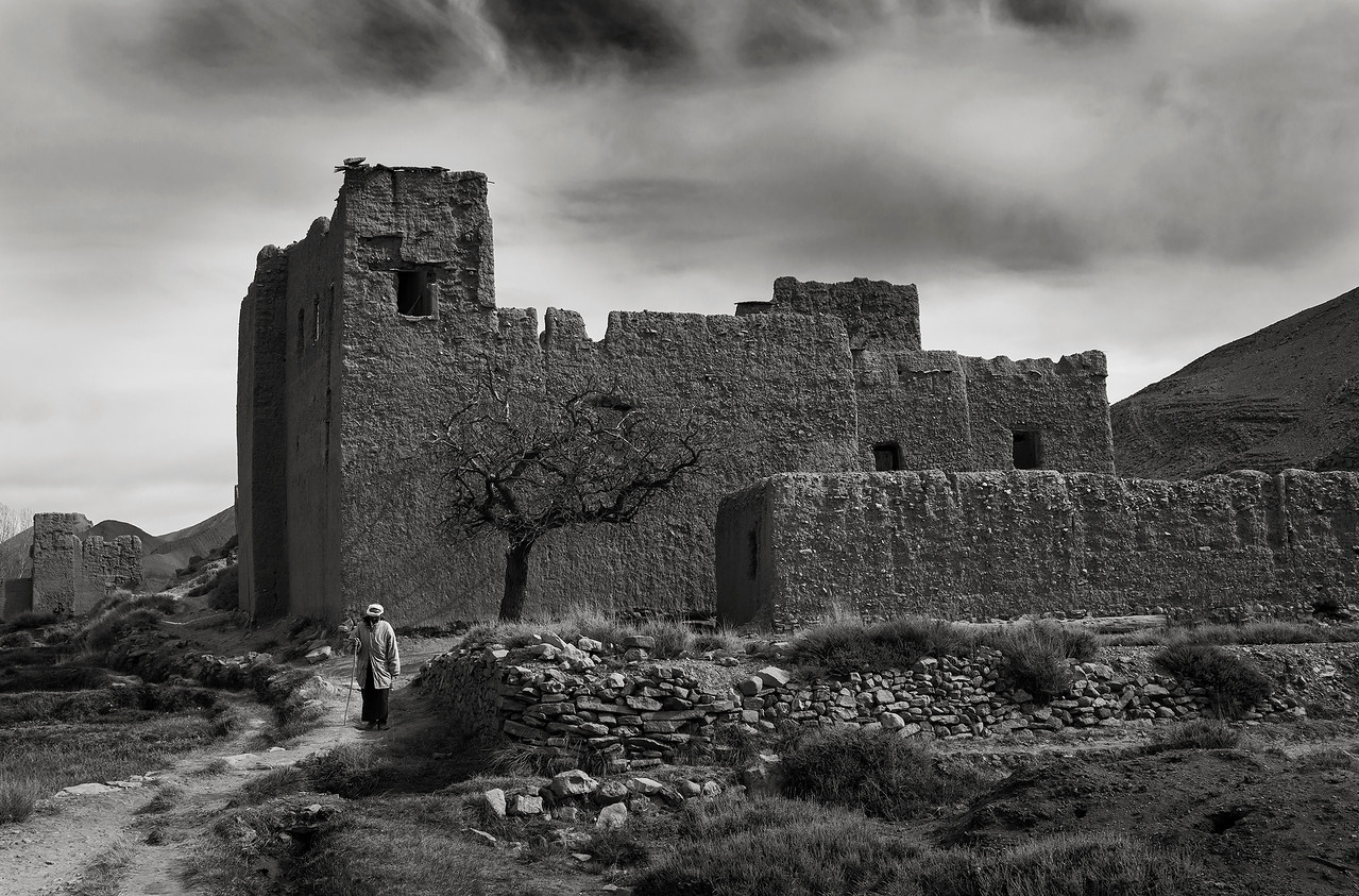An old man walking past the ruins of an old Ksar.<br /> <br /> Tamtetoucht, Morocco, 2018