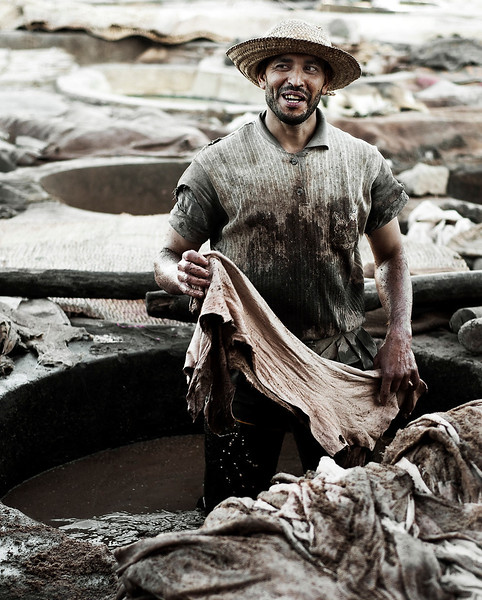Morocco is a hot, dry place. To work in a tannery in Marrakech is to work under some of the harshest working conditions there are. Not only are you exposed to the blazing sun, but you are are soaked in blood, animal bodily fluids and parts, pigeon poo, and get paid appallingly.But there is some science to the ancient Moroccan tannery tradition.Legend has it that the tanners are descended from demons who lived under a black king. As they didn't obey his rules, they were condemned to work in the tanneries. They use hundreds of concrete vats to process animal skins which are bought locally in the souks. The skins (mainly sheep and goat although cow and camel are sometimes used - lions are no longer used as they were hunted to extinction in the region around 1900) are treated far differently to the way leather is treated in other parts of the world as the process clings to its ancient traditions. Hair and flesh are removed by soaking the skins in quicklime (Calcium Oxide formed when limestone - calcium carbonate - decomposes) and water. After this, the skins are placed in a vat of water and blood, then separated and rung out, before being coloured using a few natural products:Pomegranate for yellow;Olive oil for shininess;Bark for various colours, presumably brown;Saffron for golden yellow;Henna for red/orange;Poppy for many other colours including white, pink, yellow, orange, red and blue.The skins are stretched out and left to dry for over 20 days in little piles that look rancid. Pigeon poo is used to soften the leather, and if anyone knows why, I would love to know. Presumably the poo is slightly acidic. Pigeon poo has actually been reported to be quite dangerous, with people almost dying after ingesting it. The poo adds to the smell of the place, with there being large pigeon coups near the top in which you could wade knee deep in the brown-smelly stuff. Tannery, <br /> <br /> Marrakesh, Morocco, 2010.